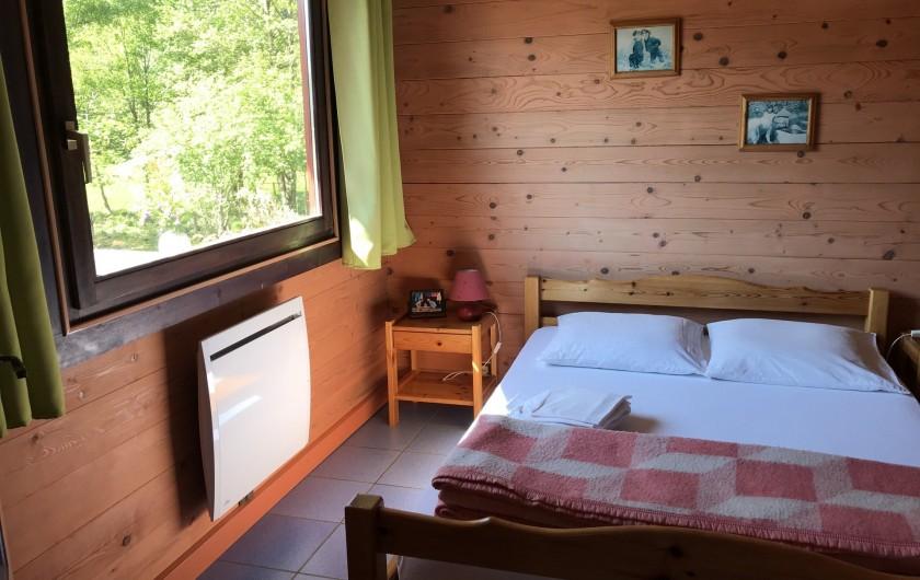 Location de vacances - Chalet à La Bresse - Chambre au RDC avec lit double, armoire et vue sur la terrasse.