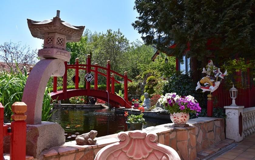 Location de vacances - Villa à Pierre-Châtel - Bassin avec le pont , lampes Japonaises  les carpes koÏ vue du salon de jardin.