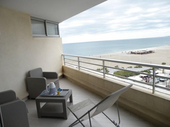 Location de vacances - Appartement à Canet-en-Roussillon - Vue de la terrasse depuis l'intérieur de l'appartement. Jour de marché en bas