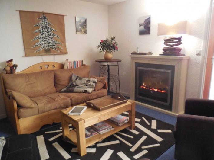 Location de vacances - Appartement à Les Menuires - Salon avec canapé lit et cheminée électrique