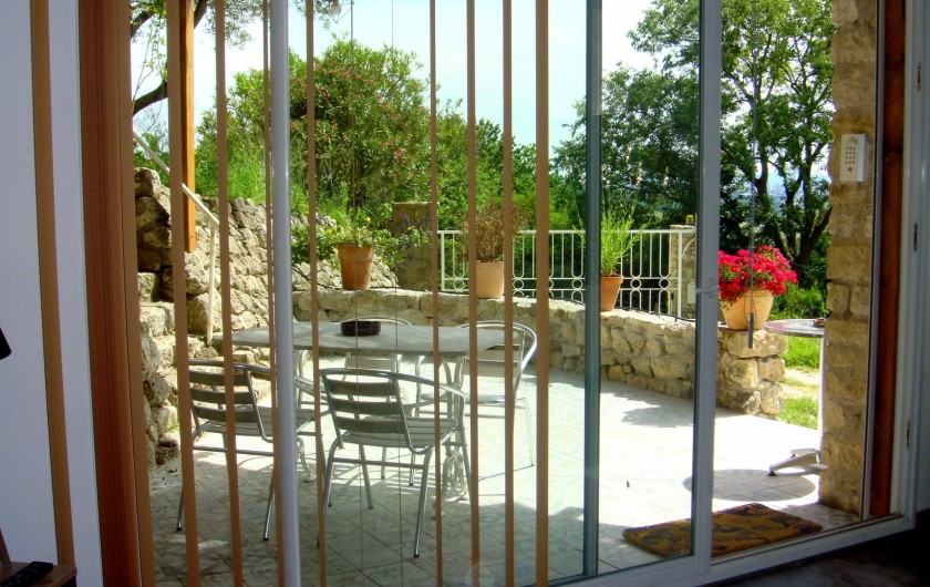 Location de vacances - Gîte à La Garde-Adhémar - Vue sur la terrasse depuis l'intérieur du gîte