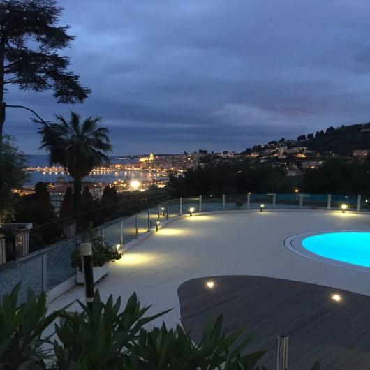 Location de vacances - Appartement à Menton - vue de la terrasse sur la piscine et sur le vieux Menton