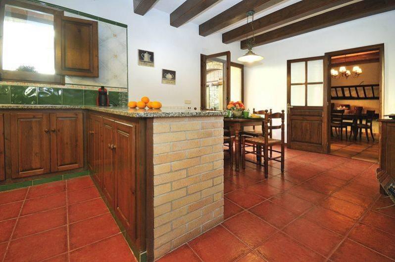 Location de vacances - Mas à Sant Antoni de Calonge - coin repas a l'interieur de la grand cuisine avec sortie à la piscine