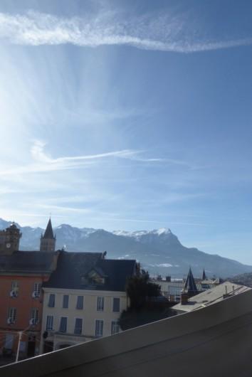 Location de vacances - Appartement à Embrun - Vue du séjour (au printemps!) : place de la Mairie, cathédrale et montagne